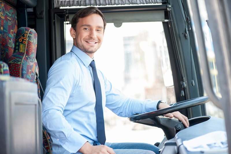 a charter bus driver prepares for a trip and smiles at passengers